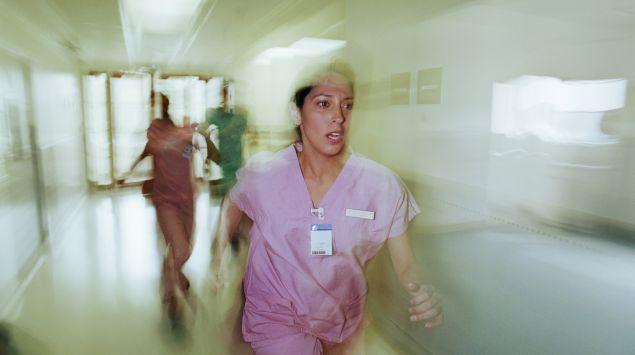 Eine Krankenschwester rennt durch einen Krankenhausgang.