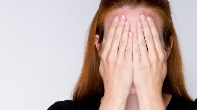 Eine Frau hält sich die Hände vor das Gesicht.