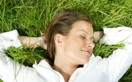 Antiallergikum: Man sieht eine glückliche Frau, die im Gras liegt.