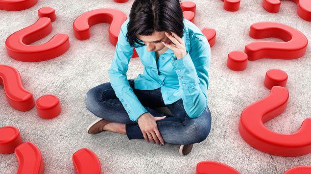 Eine Frau sitzt auf dem Boden inmitten von Fragezeichen.