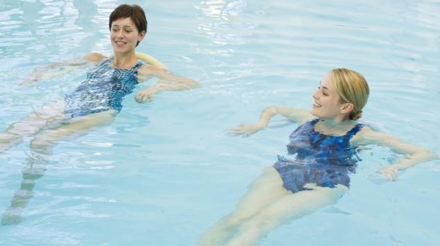 Man sieht zwei junge Frau die Aquafitness machen.