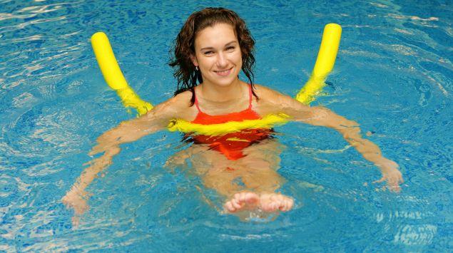 Eine junge Frau mit Schwimmnudeln im Wasser.