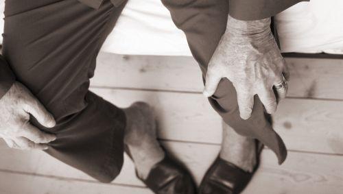 Das Bild zeigt einen älteren Mann, der an sein Knie passt.