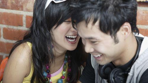 Ein junge Asiatin lachte einen jungen Asiaten an.