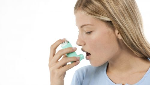 Das Bild zeigt eine Frau, die ein Asthmaspray inhaltiert.