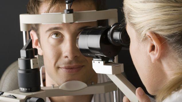 Augenärztin untersucht einen Patienten mit der Spaltlampe.