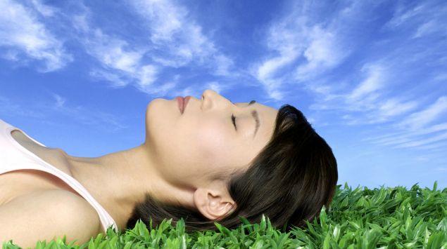 Eine Frau liegt unter blauem Himmel mit geschlossenen Augen auf einer Wiese.
