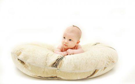 Ein Baby liegt auf einem Kissen.