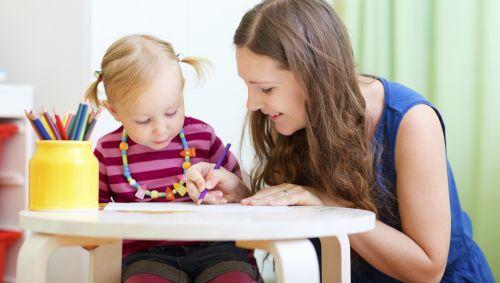 Das Bild zeigt ein kleines Mädchen, das mit seinem Babysitter malt.