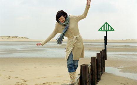 Eine Frau balanciert am Strand auf einem Holzpfosten.