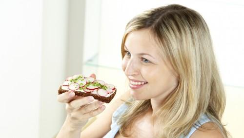 Das BIld zeigt eine junge Frau, die eine Scheibe Vollkornbrot isst.