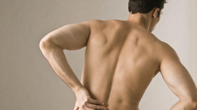 Das Bild zeigt einen Mann, der sich an den Rücken fasst.