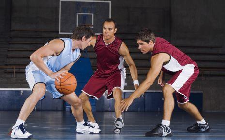 Das Bild zeigt mehrere Basketballspieler mit hochgeschnittenen Schuhen, die vor einer Distorsion schützen sollen
