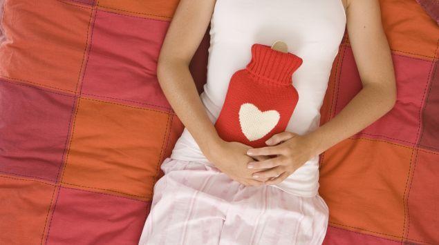 Das Bild zeigt eine Frau im Bett liegend, die eine Wärmflasche auf ihrem Bauch festhält.
