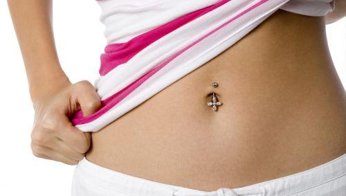 Der Bauch eines jungen Mädchens mit einem Bauchnabelpiercing.