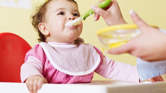 Das Bild zeigt ein Baby, das gefüttert wird.
