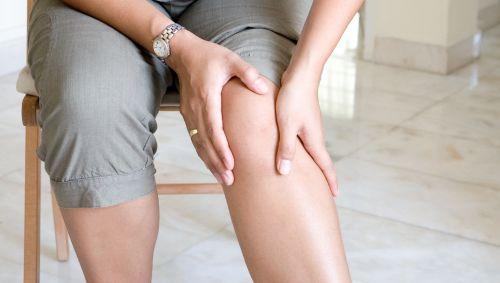 Das Bild zeigt eine Frau, die sich an den Unterschenkel greift.