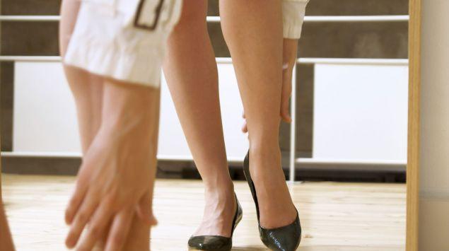 Eine Frau steht vor einem Spiegel und greift nach dem rechten Schuh.