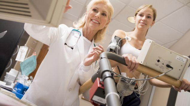 Das Bild zeigt eine junge Frau, die auf einem Laufband eine EKG-Untersuchung