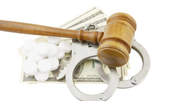 Geldscheine, Handschellen und Tabletten sowie ein Gerichtshammer.