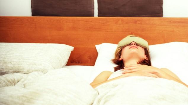 Das Bild zeigt eine Frau, die im Bett liegt und einen Lappen auf der Stirn trägt.