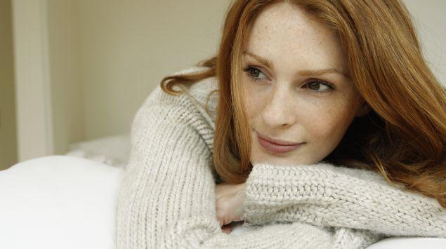 Das Bild zeigt eine Frau im mittleren Alter, die nachdenklich schaut.