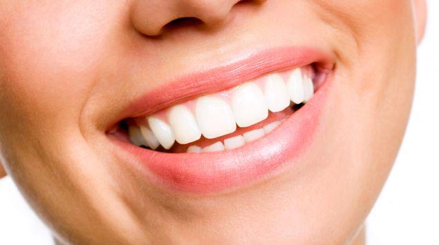 Das Lächeln einer jungen Frau mit strahlen weißen, geraden Zähnen.