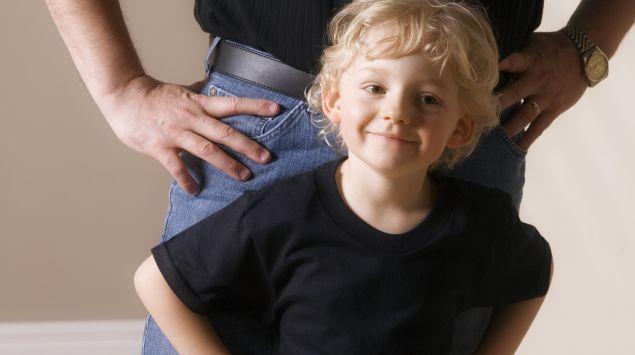 Das Bild zeigt einen kleinen Jungen und einen Mann, der im Hintergrund steht.