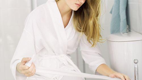 Das Bild zeigt eine Frau im Bademantel, die auf der Toilette sitzt und Klopapier abwickelt.