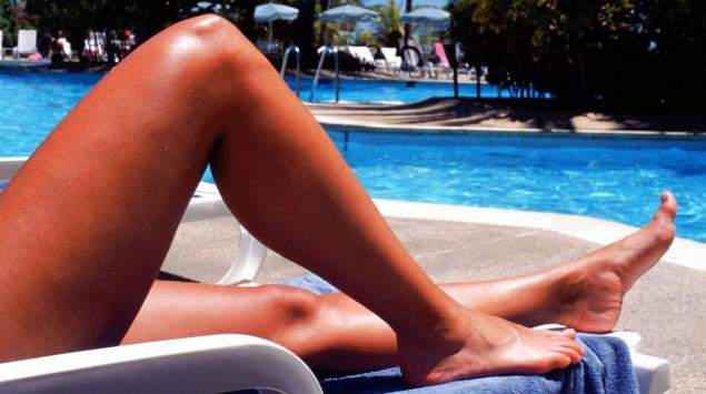 Man sieht die gebräunten Beine einer Person, die an einem Pool liegt.