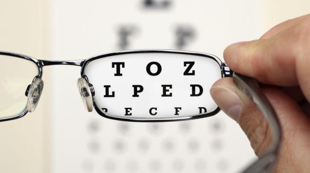 Das Bild zeigt eine Brille durch die man einen Sehtest sieht.