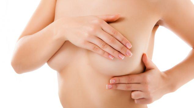 Man sieht eine Frau, die ihre Brust untersucht.