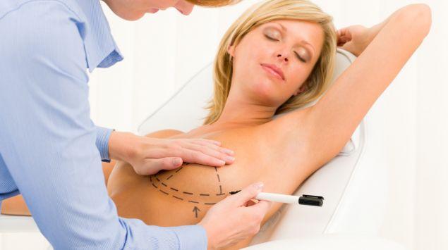 Das Bild zeigt eine Frau die Striche auf die Brust gemalt bekommt.