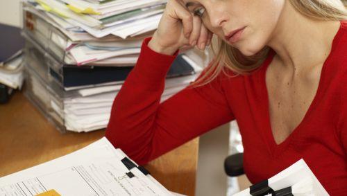 Das Bild zeigt eine Frau am Schreibtisch über Papieren sitzend.