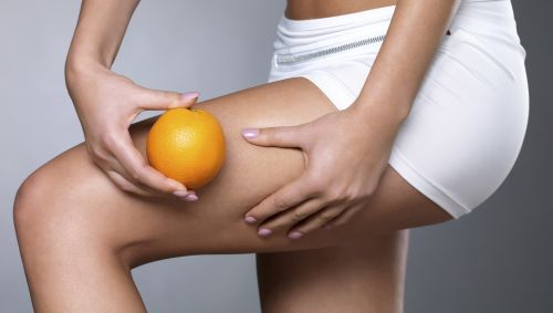 Das Bild zeigt den nackten Oberschenkel einer Frau, die eine Orange daneben hält.