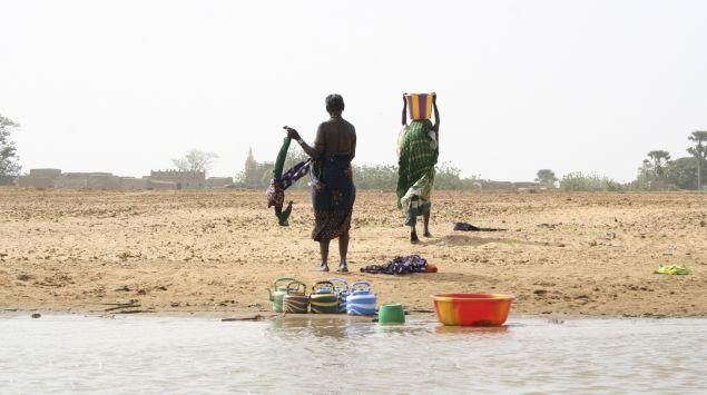 Das Bild zeigt zwei afrikanische Frauen am Wasser.