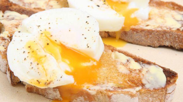Das Bild zeigt Brote mit Butter und pochierten Eiern darauf.