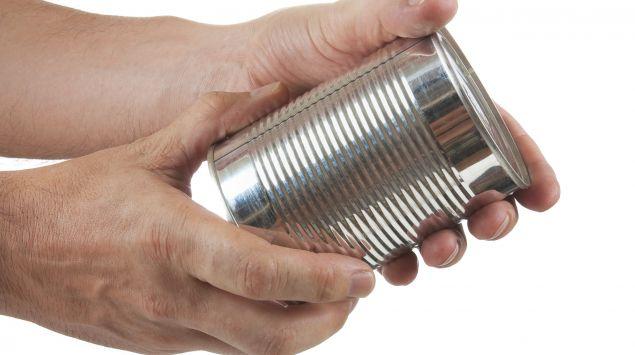 Das Bild zeigt Hände, die eine Konservendose in der Hand halten.