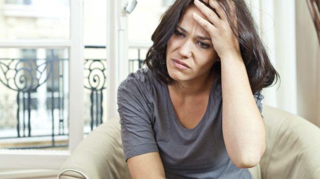 Eine Frau sitzt auf dem Sofa und fasst sich mit schmerzverzerrtem Gesicht an die Stirn.