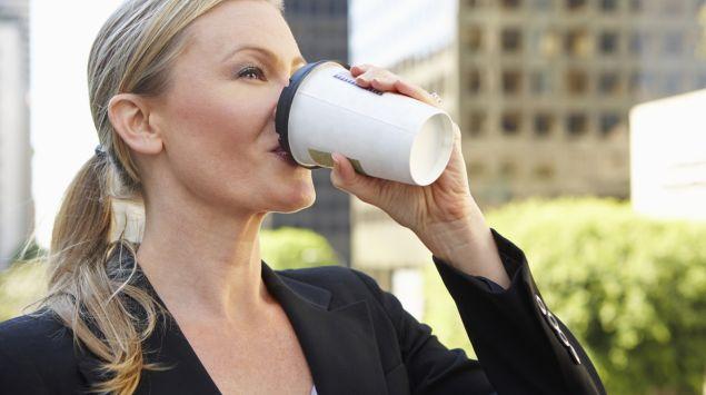 Man sieht eine Frau, die Kaffee aus einem Becher trinkt.