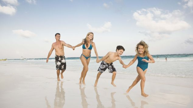 Das Bild zeigt eine Familie am Strand, die sich an den Händen hält.