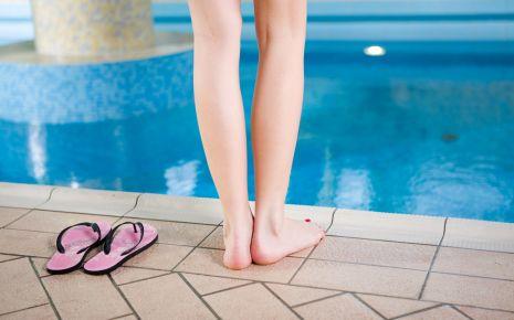 Das Bild zeigt eine Frau am Schwimmbeckenrand.
