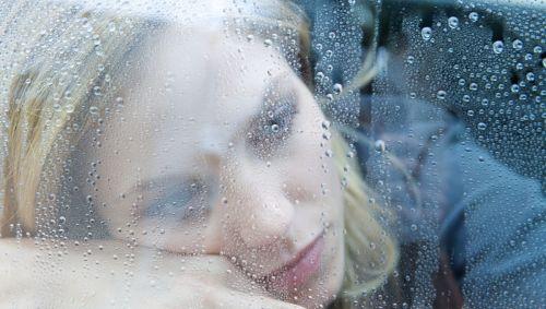 Eine depressiv aussehende Frau schaut durch ein mit Regentropfen bedecktes Fenster.