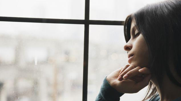 Das Bild zeigt eine junge Frau, die traurig aus dem Fenster guckt.