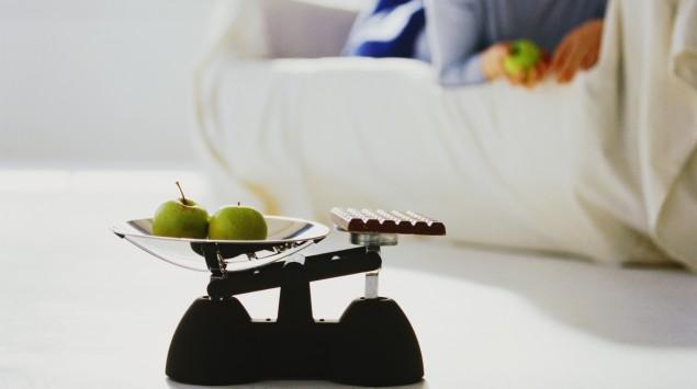 Das Bild zeigt eine Waage mit Äpfeln und Schokolade. Im Hintergrund liegt eine Frau auf einem Sofa.