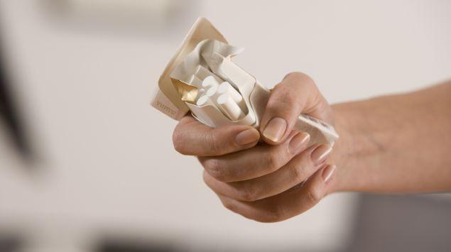 Das Bild zeigt eine Hand, die eine Packung Zigaretten zerdrückt.