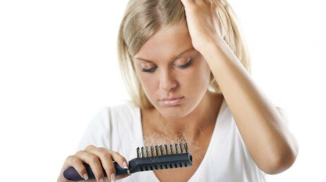 Das Bild zeigt eine Frau, die af die Haare in ihrer Bürste schaut.