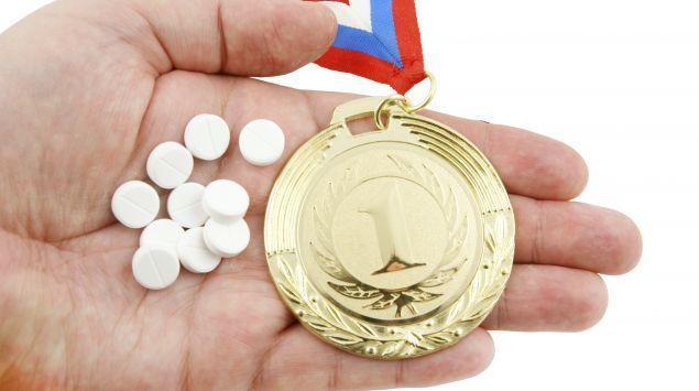 Das Bild zeigt eine Handfläche, in der Tabletten und eine goldene Medaille liegen.