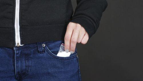 Jemand zieht ein Päckchen mit weißen Pulver aus seiner Hosentasche.