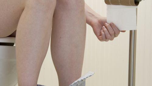 Das Bild zeigt eine Frau auf Toilette.